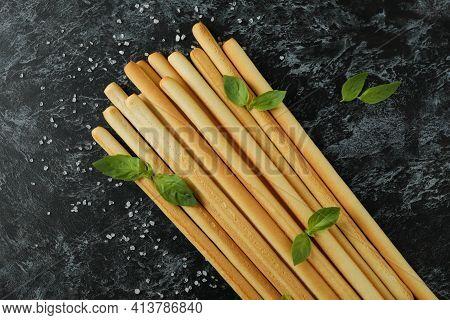 Grissini Breadsticks With Salt And Basil On Black Smoky Background