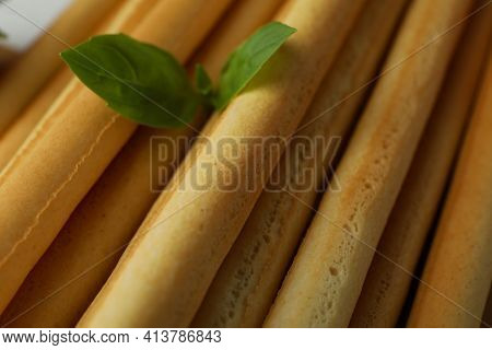 Grissini Breadsticks With Basil On Whole Background, Close Up