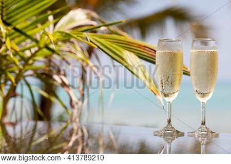 Two Glasses Of Chilled Prosecco Over Tropical Background