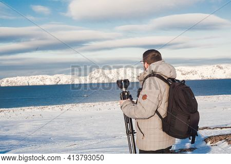 North Sea Coast With Ice And Snow. Man Blogger At Europe Travel Adventure Trek. Person Wearing Hat A