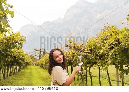 Young Woman With A Glass Of White Wine In The Vineyards Of Italy. Person Pouring Wine. Free Space Fo