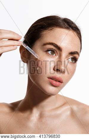 Beauty Woman With Freckles, Naked Shoulders And Nude Face, Apply Serum Vitamin C, Argan Oil Tea Tree