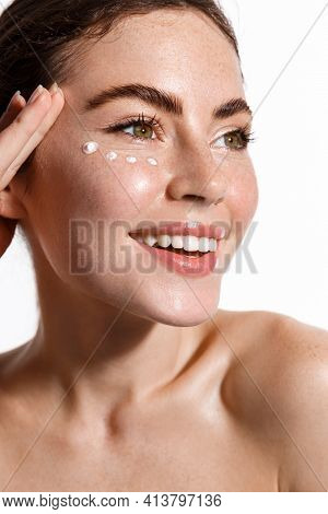 Close Up Beauty Portrait Of Girl Freckles, Nude Naked Skin, Applying Facial Cream Under Eye For Anti