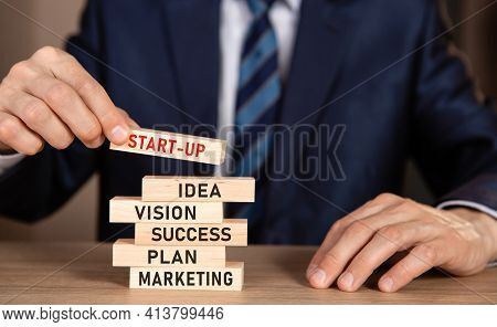 Man In Suit Building Wooden Blocks With Text Start-up, Ideas, Vision, Success, Plan, Marketing. Inve