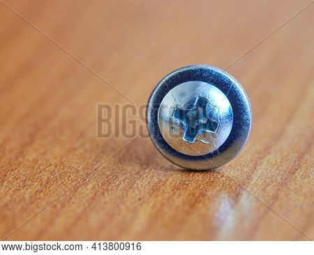 Close-up Macro Self-tapping Screw Made Of Galvanized Steel On A Wooden Table