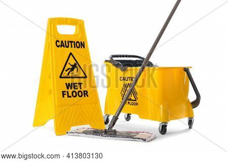 Safety Sign With Phrase Caution Wet Floor, Mop And Bucket On White Background. Cleaning Service