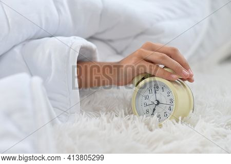 Girl Awaked Up In Her Bed. Hand On Alarm Clock