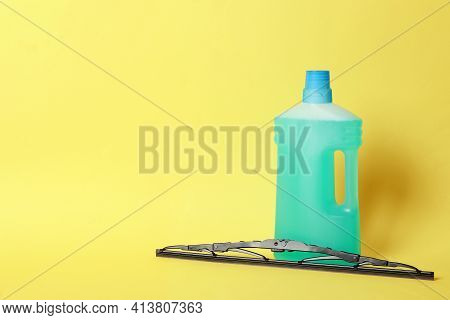 Bottle Of Windshield Washer Fluid And Wiper On Yellow Background. Space For Text