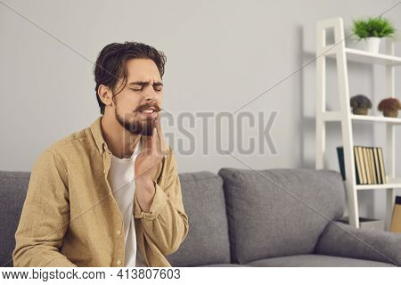 Young Man Suffering From Acute Toothache And Touching Cheek With Grimace Of Pain