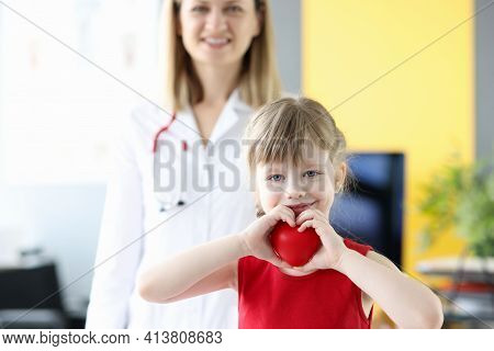 Little Girl Holding Red Toy Heart In Her Hands In Doctors Office