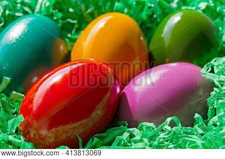 Colorful Dyed Easter Eggs In A Green Paper Nest. Multicolored Paschal Eggs, Arranged In A Nest, Made