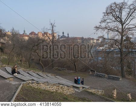Czech Republic, Prague, February 23, 2021: Group Of People, Mother And Childern Sitting At Garden Al