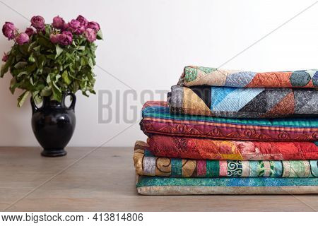 Quilts Stack And A Bouquet Of Dried Roses In A Vase On White Wall Background