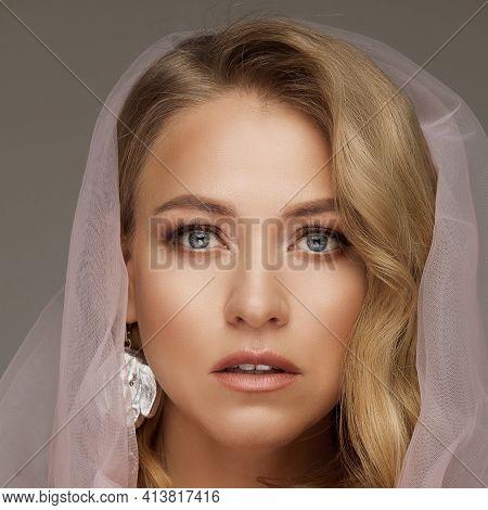 Stunning Blonde Model In Pink Veil. Natural Make-up Wearing Pink Veil And Holding Fragile Pink Rose.