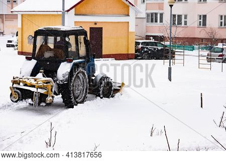 The Tractor Clears The Road From Snow In Winter During A Snowfall.