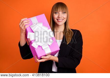 Portrait Of Charming Cheerful Girl Holding In Hands Festal Giftbox Isolated Over Bright Orange Color