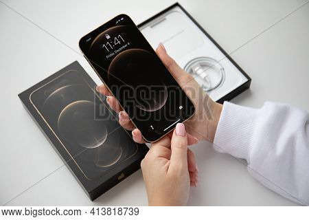 Alanya, Turkey - December 4, 2020: Woman Hand Holding Box Iphone 12 Pro Max Gold With Home Screen Io