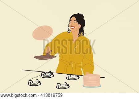 Pretty Woman In A Yellow Bathrobe Throws Up Pancake On A Frying Pan On Gas Stove. Cooking A Sweet Br
