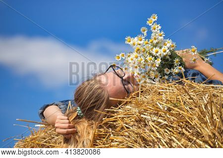 Girl With A Bouquet Of Daisies On A Background Of Blue Sky