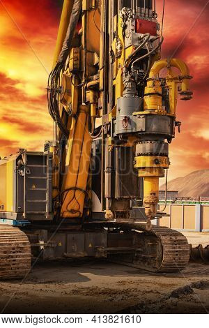 Hydraulic Drilling Rig Against The Backdrop Of The Sunset Sky. Installation Of Bored Piles By Drilli