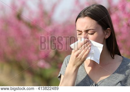 Woman Blowing On Tissue Suffering Allergy In Spring In A Field Of Peach Trees