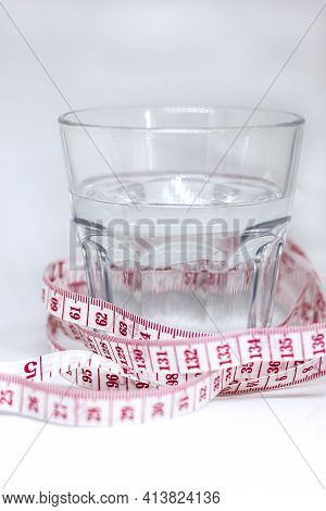 Measuring Tape Centimeter Meter And Defocused Glass Of Water On White Background, Healthy Lifestyle