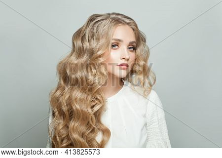 Nice Woman With Healthy Blonde Curly Hairdo On White Background