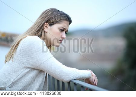 Sad Woman Looking Down In A House Balcony Complaining Alone In A Town