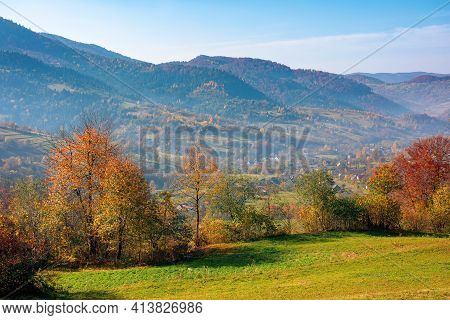 Mountainous Rural Landscape In Autumn. Trees The Edge Of A Hill In Colorful Foliage. Sunny Day With