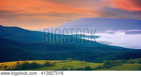 Mountainous Rural Landscape At Sunrise. Trees And Agricultural Fields On Hills Rolling In To The Dis