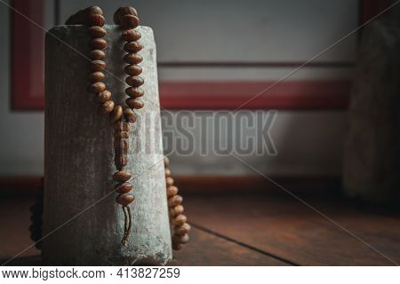 Rosary Hanging On Stone. Rosary Photo Focused With Natural Light In The Mosque. Inside Mosque Photo.