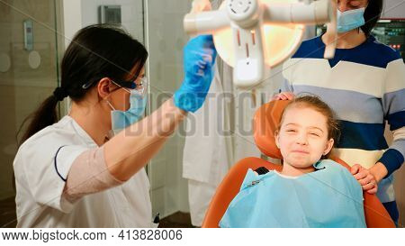Woman Stomatologist Technician Lighting The Lamp For Examining Little Patient