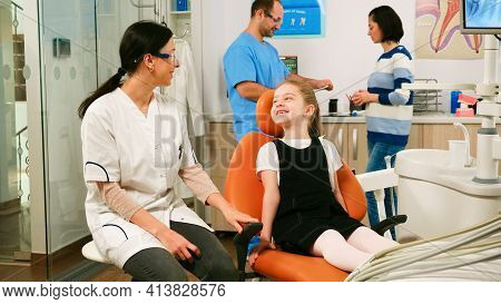 Little Girl Patient Waiting Pediatric Stomatologist Woman Sitting In Dental Chair