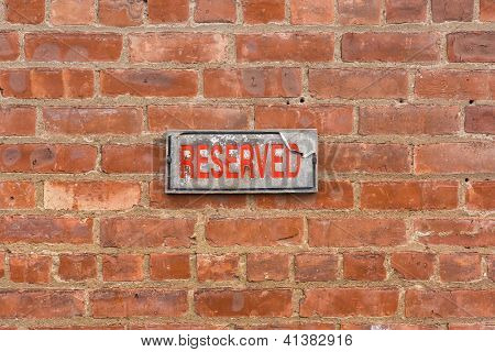 Reserved sign on brick wall