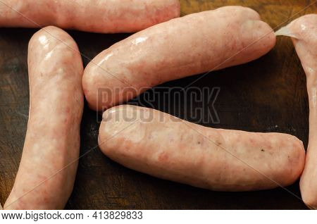 Raw Classic British Sausage Made From Prime Cuts Of Pork On The Wooden Board