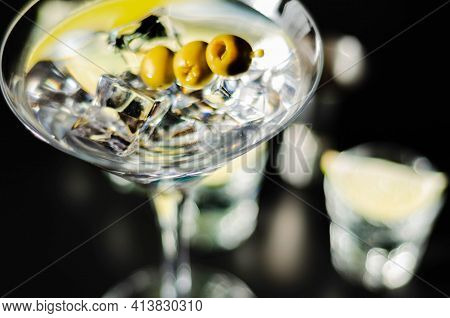 Traditional Drink Based On Gin And Vermouth With Olives And Ice Cubes In A Cocktail Glass