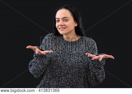 Woman With Long Dark Hair Wearing Gray Knitted Sweater On A Black Background  Gesticulating With Her