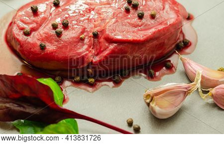 Raw Beef Sirloin Steak With Peppercorns And Garlic Prepared For Frying