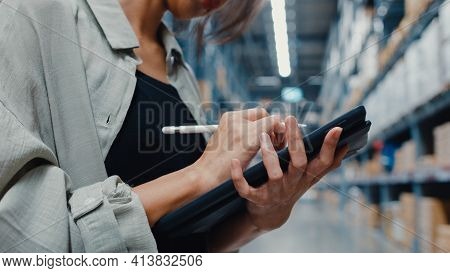 Attractive Young Asia Businesswoman Manager Looking For Goods Using Digital Tablet Checking Inventor