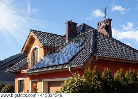 Solar Panels On The Roof Of A Beautiful Modern Home. Rays Of The Sun.