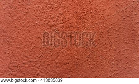 A Fragment Of A Wall Painted In A Bright Terracotta Color. Painted Plaster, Concrete. Natural Volume