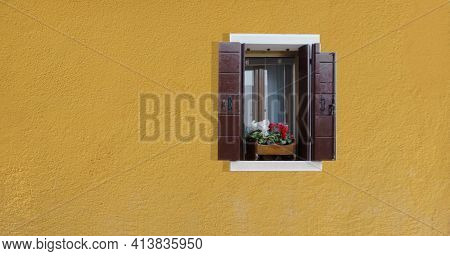 A Rectangular Window With Open Brown Shutters On A Yellow Wall, White And Red Indoor Flowers Growing