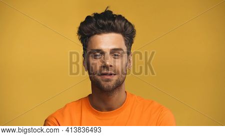 Good-looking Man Looking At Camera Isolated On Yellow.