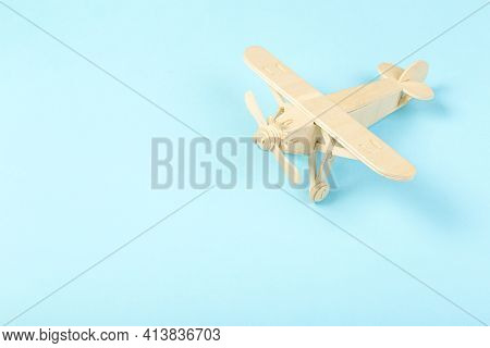 Model Of A Wooden Toy Plane, Airliner, On A Blue Background. The Concept Of Travel And Transport And