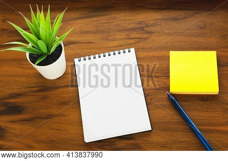 The Flower, Notepad And Stickers Are Located On The Surface Of The Writing Desk. Workplace, Flat Lay