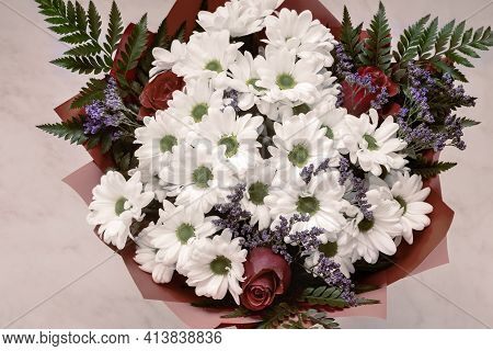 A Beautifully Designed Bouquet Of White Chrysanthemums And Red Roses On A Light Background. Top View