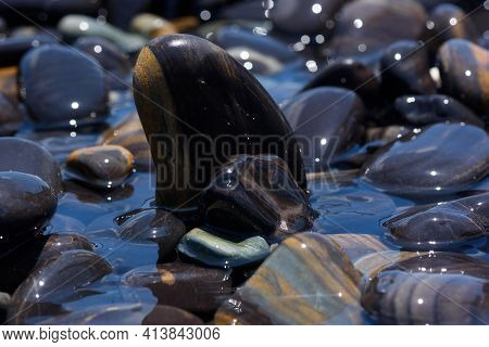 Close-up View Of Beautiful Smooth Black Stones On The Beach At Koh Hin Ngam, Satun, Thailand.