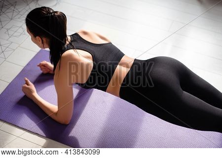 Woman In Sportswear Doing Plank Exercise On Yoga Mat