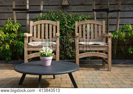 Cozy Seating Area In The Garden Of A Modern Home In The Spring, Wooden Seats With Colorful Flowers I