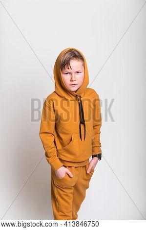 Kid In Hood From Yellow Fashion Sport Suit Hoodie. Blond Kid Face In A Hood Looks From Under A Foreh